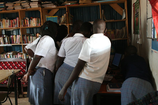 Pupils of the Girls Soccer Academy in Kibera work with the laptops