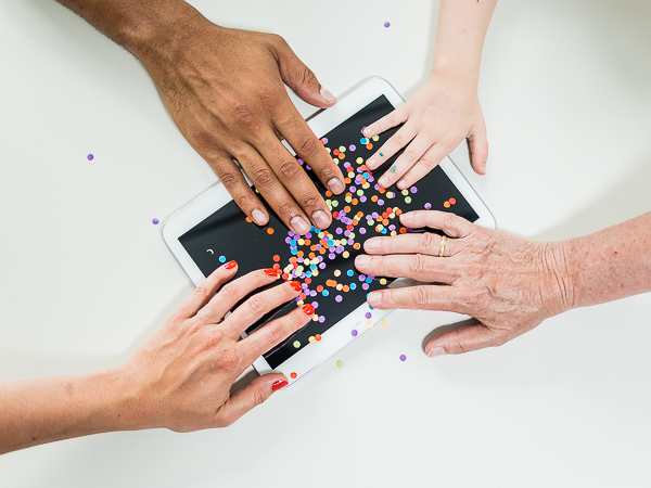 Four different hands from all gender, race and age are holding a tablet computer littered with confetti