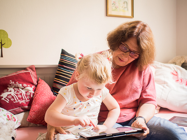 An elderly person and a young girl working with a tablet computer